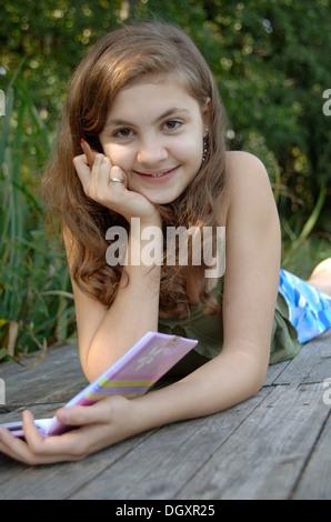 Teenage girl sitting on a boardwalk avec un livre et un stylo dans sa main Banque D'Images