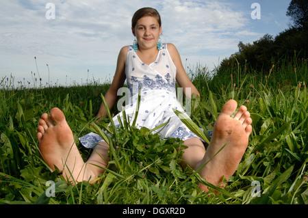 Teenage girl porte une robe assis avec les pieds nus dans l'herbe Banque D'Images