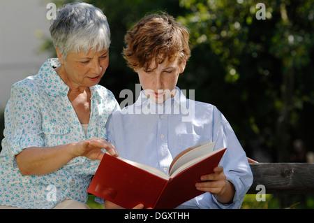 Grand-mère et petit-fils sont à la recherche à un livre rouge ensemble sur banc de parc