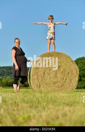 Les femmes enceintes, en neuf mois, et fille, six ans, debout sur une balle de paille Banque D'Images