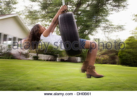 Mixed Race girl playing on tire swing Banque D'Images
