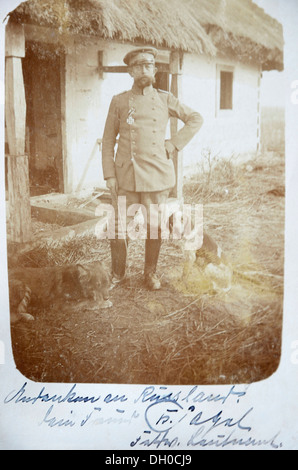 Carte postale, sur le terrain, officier allemand portant une médaille avec les chiens de chasse en face d'une maison au toit de chaume en Galice, campagne de Russie