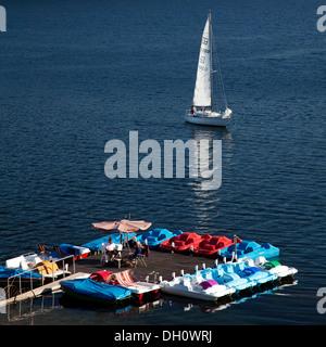Un bateau à voile à proximité d'un service de location de bateaux à pédales sur le lac Sorpesee ou Sorpe, Langscheid, Banque D'Images