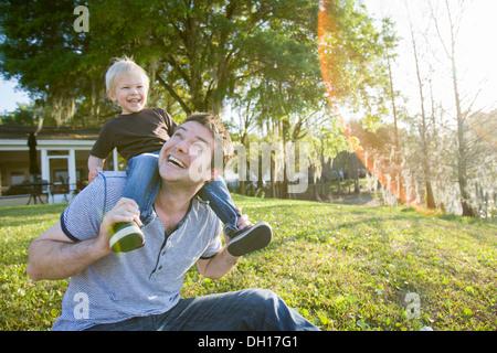 Woman carrying son on shoulders in backyard