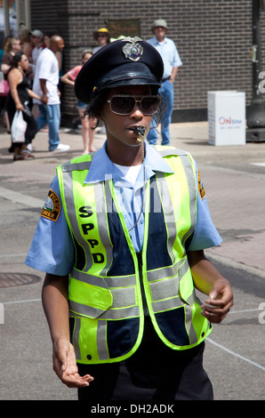 Black police woman calmement diriger la circulation. Grand Old Day Festival St Paul Minnesota MN USA Banque D'Images