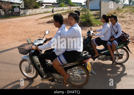 Les enfants de l'école portrait horizontal sur les cyclomoteurs équitation accueil après l'école. Banque D'Images