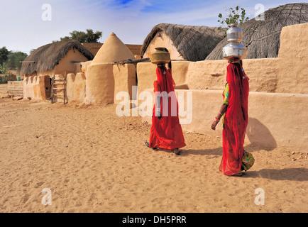 Deux femmes indiennes portant des saris rouges portant de l'eau remplie de bidons sur leurs têtes à travers un village, Banque D'Images