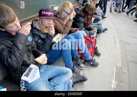Londres, Angleterre, Royaume-Uni. Les jeunes gens assis à Trafalgar Square, manger des sandwiches Banque D'Images