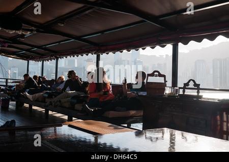 Les touristes se détendre à bord d'un bateau jonque traditionnelle à Hong Kong. Banque D'Images