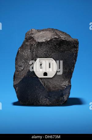 Un grand morceau de charbon noir avec une seule prise électrique. Fond bleu lumineux Banque D'Images