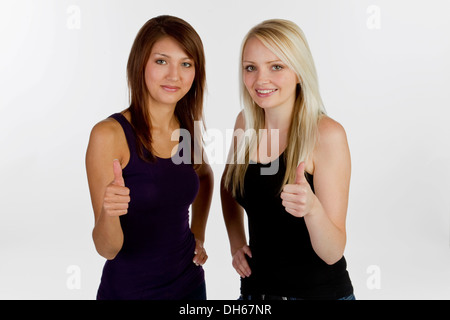 Deux smiling young women making Thumbs up geste Banque D'Images