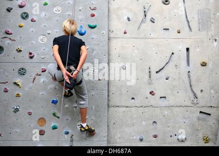 Top-rope alpiniste dans le centre d'escalade Hambourg Kletterzentrum coating ses mains avec de la craie pour une Banque D'Images