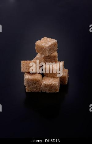 Photo de cubes de sucre isolé sur un fond noir Banque D'Images