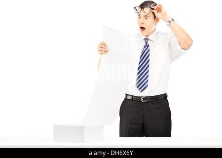 Jeune homme choqué la lecture d'un document Banque D'Images