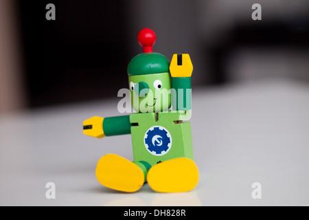 Un mignon petit robot jouet en bois, s'asseoir, de l'étirement. Banque D'Images