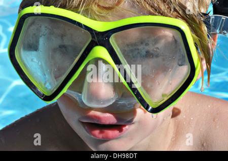 Un garçon portant un masque dans la piscine Banque D'Images