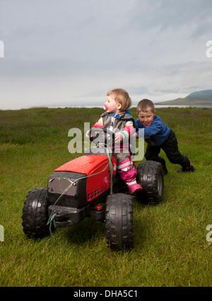 Jeune garçon en poussant sa jeune sœur sur tracteur jouet, Eskifjordur, Islande Banque D'Images