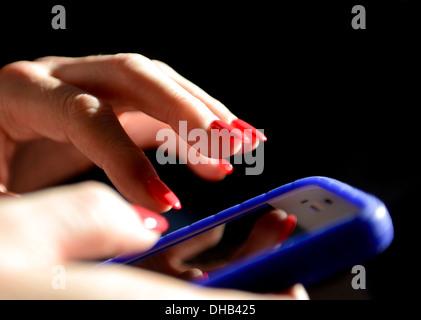 A womans mains près des ongles peints en rouge tenant un téléphone intelligent Banque D'Images