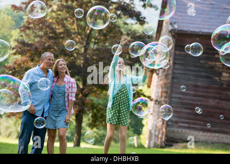 Une famille assis sur l'herbe à l'extérieur d'un bar, faire des bulles et de rire. Banque D'Images