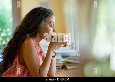 Une femme assise seule dans un café, le café. Banque D'Images