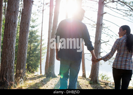 Directement au bord du lac. Un couple en train de marcher dans l'ombre des pins en été. Banque D'Images