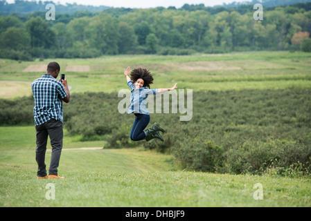 Un homme de prendre une photo d'une femme en sautant en l'air, sautant de joie avec ses bras tendus. Banque D'Images