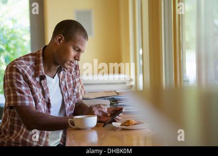 Un homme assis avec une tasse de café, tenant une tablette numérique. Banque D'Images