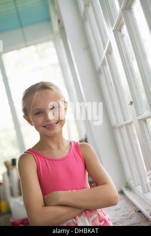 Une jeune fille dans une cuisine portant une robe rose.