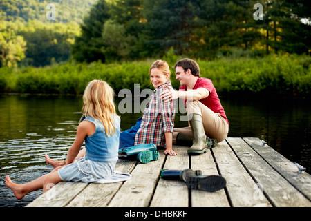 Trois personnes, deux adultes et un enfant se détendre sur un ponton, les pieds dans l'eau à la fin d'une journée. Banque D'Images