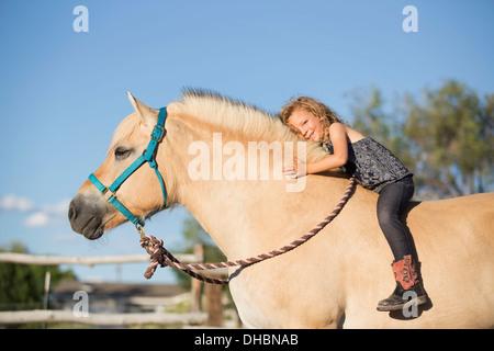 Une jeune fille assise sur un cheval. Banque D'Images