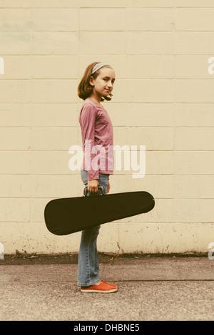Une fillette de dix ans portant un violon dans un cas sur une rue urbaine. Banque D'Images