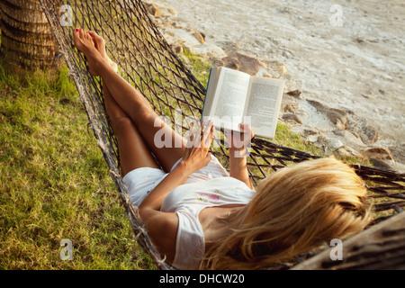Femme couchée dans un hamac sur la plage et bénéficiant d'une lecture de livres Banque D'Images