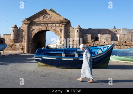 L'homme musulman de marcher en dessous de la vieille ville et remparts, Essaouira, Côte Atlantique, Maroc, Afrique du Nord, Afrique