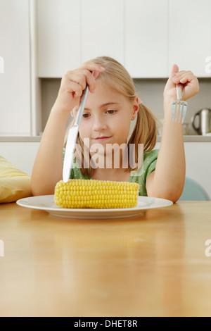Girl piquer sur la plaque d'épis de maïs Banque D'Images