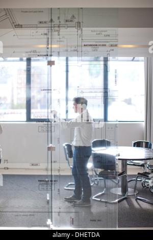 Dessin homme plans architecturaux sur mur de verre Banque D'Images