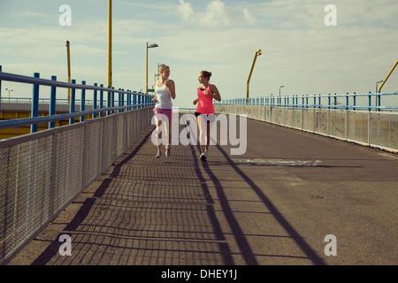 Jeune femme joggers fonctionnant sur bridge Banque D'Images