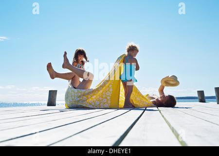 Jeune famille couchait sur pier, Utvalnas, Gavle, Suède Banque D'Images