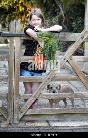 Girl in garden holding bunch of carrots Banque D'Images