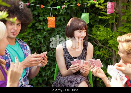 Groupe de jeunes amis des cartes à jouer dans le jardin Banque D'Images