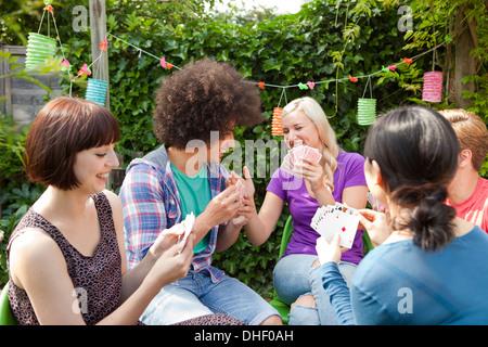 Groupe de jeunes amis adultes cartes à jouer dans le jardin Banque D'Images
