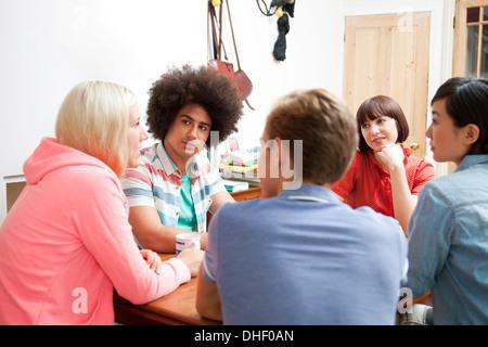 Groupe de jeunes amis adultes assis autour d'une table de cuisine Banque D'Images