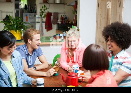 Groupe de jeunes amis discutant autour d'une table de cuisine Banque D'Images