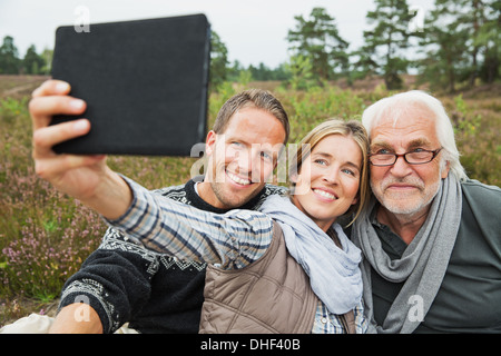 Woman holding digital tablet taking photograph Banque D'Images