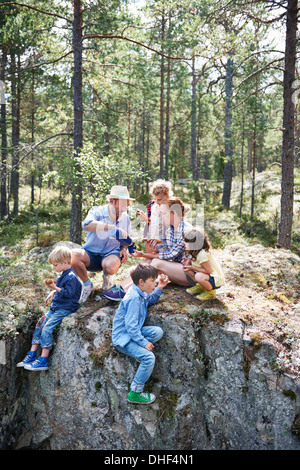 Family sitting on rocks in forest eating picnic Banque D'Images