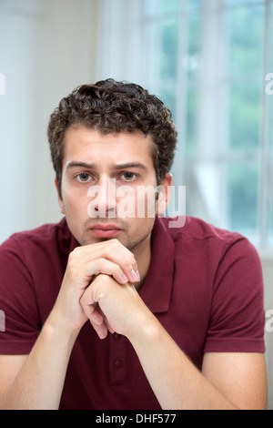 Young man resting chin on mains jointes Banque D'Images