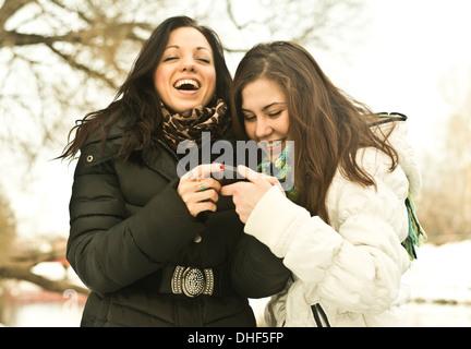 Deux jeunes femmes riant de téléphone mobile au parc en hiver Banque D'Images
