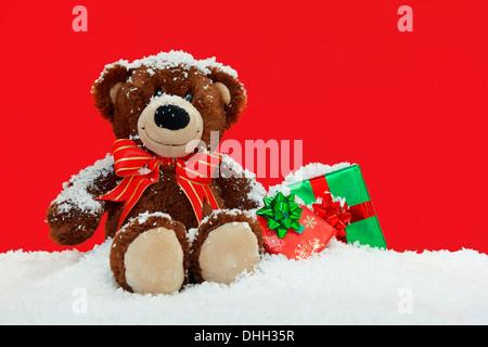 Un ours en peluche fait main assis dans la neige avec gift wrapped Christmas presents sur un fond rouge. Banque D'Images