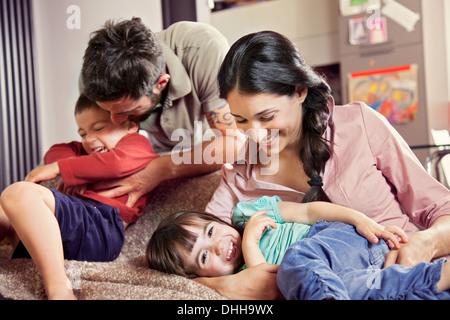 Famille avec deux enfants jouant sur canapé Banque D'Images