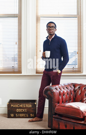 Portrait of young man holding coffee mug in living room Banque D'Images