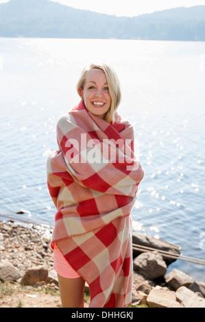 Jeune femme enveloppée dans une couverture par le lac, Hadley, New York, USA Banque D'Images